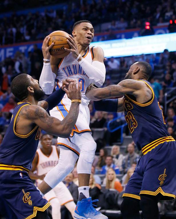 . Oklahoma City Thunder guard Russell Westbrook (0) drives between Cleveland Cavaliers guard Kyrie Irving, left, and forward LeBron James during the third quarter of an NBA basketball game in Oklahoma City, Thursday, Feb. 9, 2017. Oklahoma City won 118-109. (AP Photo/Sue Ogrocki)