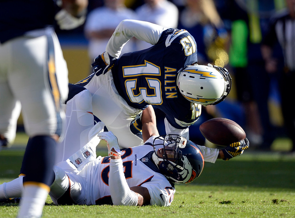 . SAN DIEGO, CA - DECEMBER 14: Denver Broncos cornerback Chris Harris (25) tackles San Diego Chargers wide receiver Keenan Allen (13) in an awkward position after his catch during the second quarter December 14, 2014 at Qualcomm Stadium.  (Photo By John Leyba/The Denver Post)