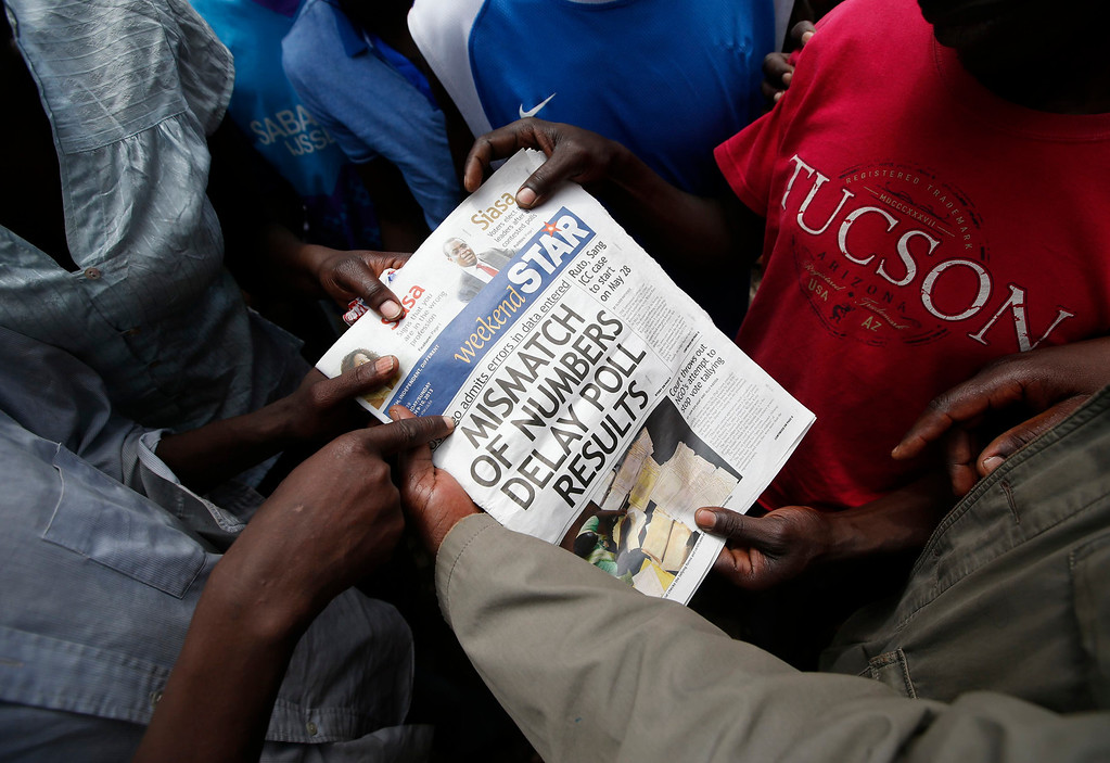 . Supporters of Kenyan Prime Minister Raila Odinga look at a newspaper in the Mathare slum in the Kenyan capital of Nairobi March 9, 2013. REUTERS/Goran Tomasevic