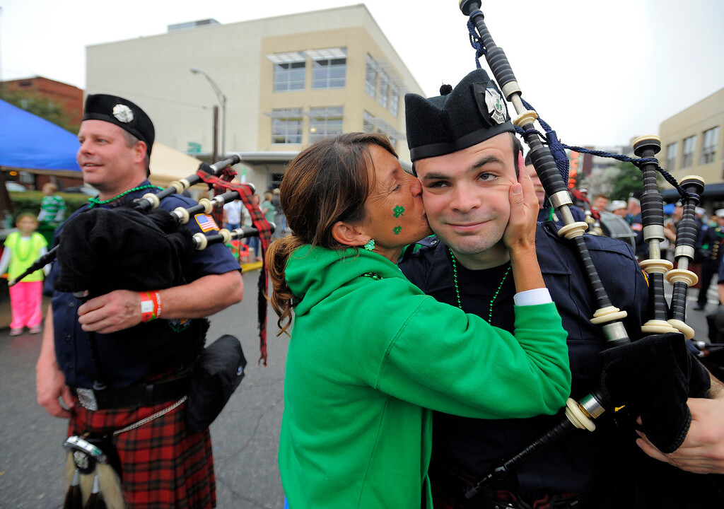 . Brenda Meyers kisses a member of the Yonkers New York Fire Department Pipe and Drum during Savannah\'s 190-year-old St. Patrickís Day parade, Monday, March 17,  2014, in Savannah, Ga. Kissing men in uniform is a tradition during the celebration..  (AP Photo/Stephen B. Morton)