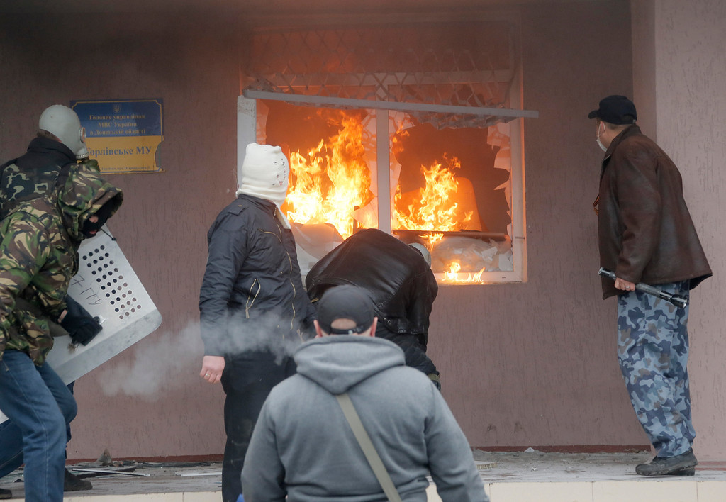 . Pro-Russian men attack a police station in the eastern Ukrainian town of Horlivka Monday, April 14, 2014. Several government buildings have fallen to mobs of Moscow loyalists in recent days as unrest spreads across the east of the country. (AP Photo/Efrem Lukatsky)