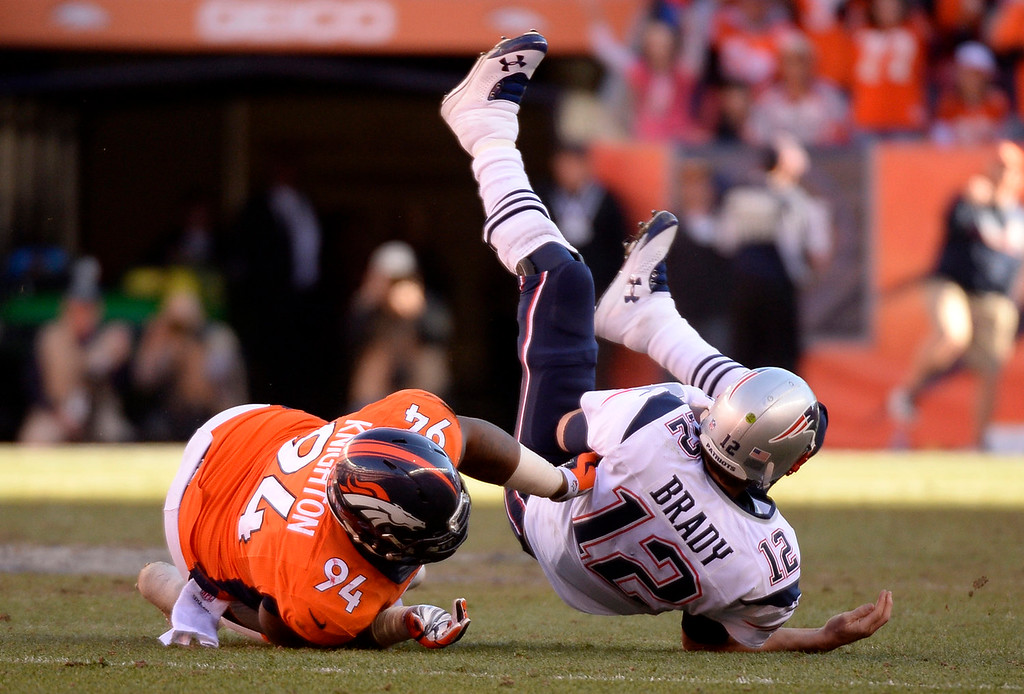 . Denver Broncos defensive tackle Terrance Knighton (94) gets a hold of New England Patriots quarterback Tom Brady (12) for a sack during the third quarter. The Denver Broncos vs. The New England Patriots in an AFC Championship game  at Sports Authority Field at Mile High in Denver on January 19, 2014. (Photo by John Leyba/The Denver Post)