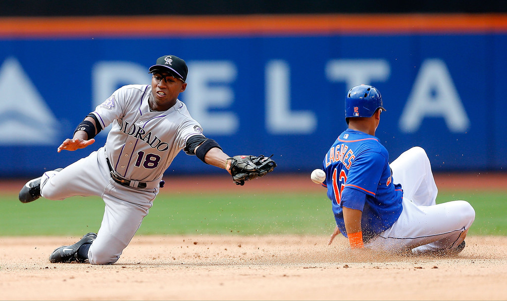 . Jonathan Herrera #18 of the Colorado Rockies can\'t come up with the throw as Juan Lagares #12 of the New York Mets steals second base in the seventh inning at Citi Field on August 8, 2013 in the Flushing neighborhood of the Queens borough of New York City. The Mets defeated the Rockies 2-1.  (Photo by Jim McIsaac/Getty Images)
