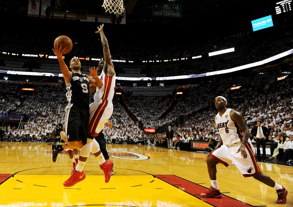 . San Antonio Spurs\' Tony Parker (L) drives to the net on Miami Heat\'s Joel Anthony as LeBron James watches during the second quarter in Game 1 of their NBA Finals basketball playoff in Miami, Florida June 6, 2013. REUTERS/Steve Mitchell/Pool
