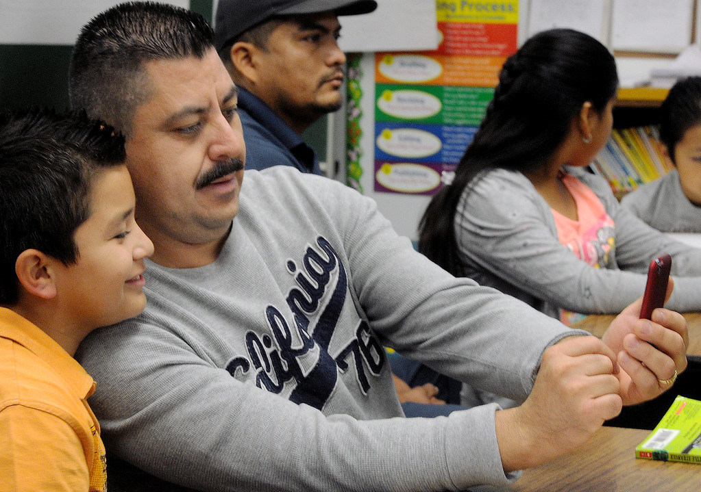 ". Benjamin Huzar, with his dad, Mario Huizar who photographs a cell phone picture of them in class at Elwin Elementary School in Baldwin Park. Elwin Elementary hosted, ""Bring Your Dad to School\"" Day Wednesday, October 2, 2013.(Walt Mancini/San Gabriel Valley Tribune)"