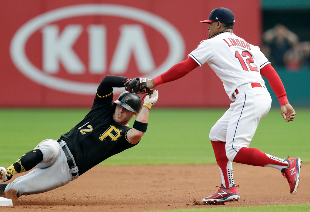 . Cleveland Indians\' Francisco Lindor, right, tags out Pittsburgh Pirates\' Corey Dickerson at second base in the first inning of a baseball game, Monday, July 23, 2018, in Cleveland. Dickerson was out on the play. (AP Photo/Tony Dejak)