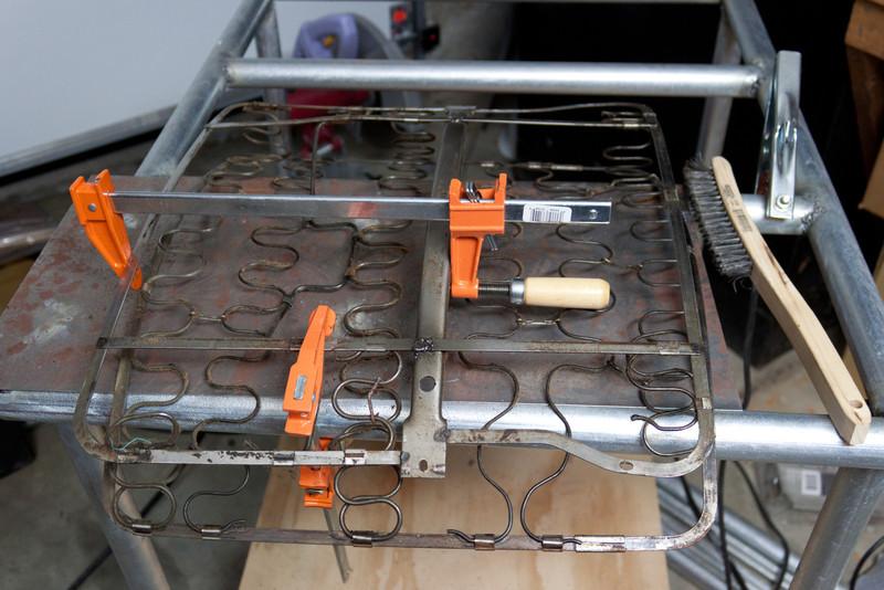 Driver's seat back spring had broken welds/metal