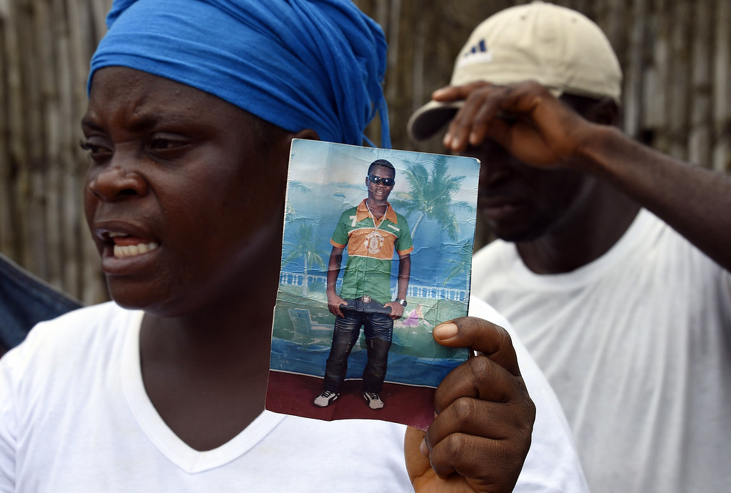 . Liberian mother Mary holds a picture of her son Emaya, 20, who is suffering from Ebola and being treated at Island Hospital in Monrovia on September 26, 2014. Mary hasn\'t had news of her son since he was admitted to the hospital on September 21. PASCAL GUYOT/AFP/Getty Images