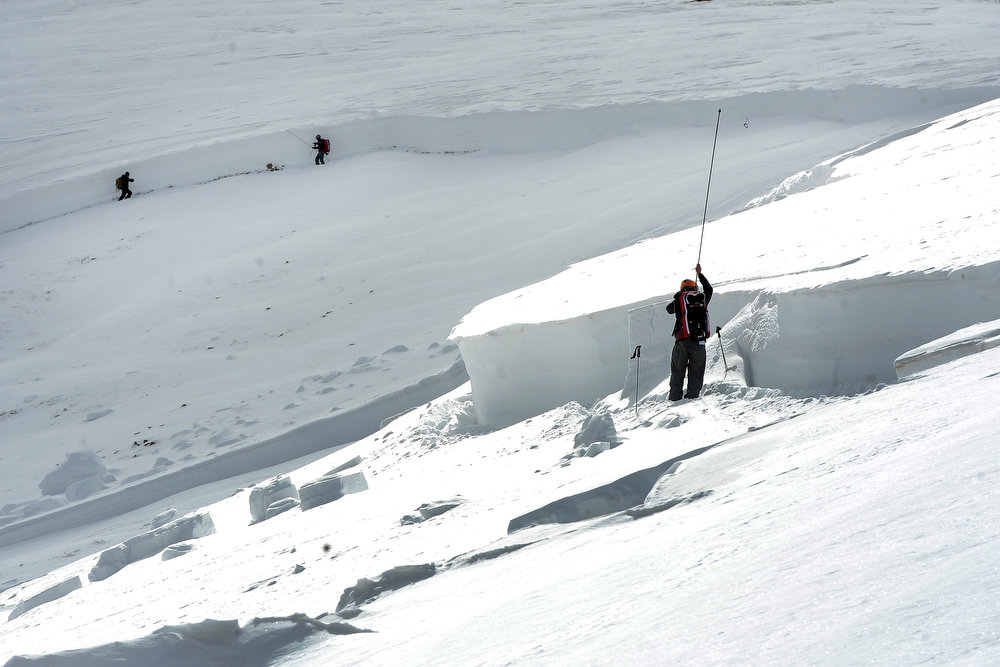 . Scott Toepfer, right, a member of the Colorado Avalanche Information Center or CAIC, takes depth measurements every 50 feet at the crown of the avalanche on April 21, 2013.  In the back round are Brian Lazar and John Snook, who walk along the crown to find an area to dig a snow pit to investigate the layers of snow where the avalanche broke off.  The avalanche occurred in an area known as  Sheep Creek near Loveland Pass on Saturday, April 20, 2013. The deadly avalanche killed 5 snowboarders. The trio are doing what is called a fracture line profile of the crown of the avalanche, or where the hard slab avalanche broke off.  They are looking for weak layers in the snow pack to help discover what contributed to the avalanche.  The avalanche was on the western flank of Mount Sniktau and happened around 2:00 pm on Saturday.  (Photo By Helen H. Richardson/ The Denver Post)