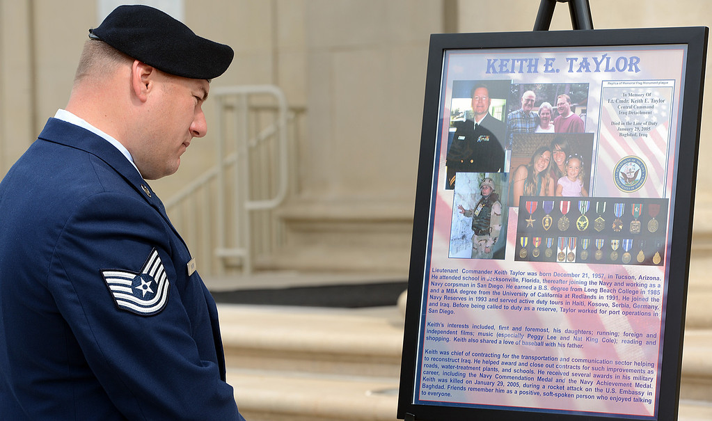 . Jason Mabon, an Air Force Reservist and University of Redlands student, looks at a poster commemorating Keith Taylor during a memorial service for fallen service members Friday May 17, 2013 in front of the Memorial Chapel at the university. The ceremony featured a special tribute to Keith Taylor, a University of Redlands alumnus and father of a University of Redlands student. He was killed serving in Iraq. (Rick Sforza/Staff photographer, Redlands Daily Facts)