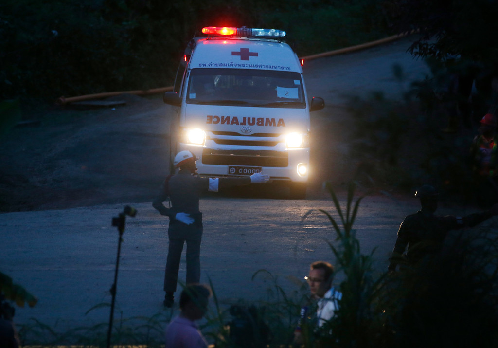 . One of two ambulances with flashing lights leaves the cave rescue area in Mae Sai, Chiang Rai province, northern Thailand, Monday, July 9, 2018. The ambulance has left the cave complex area hours after the start of the second phase of an operation to rescue a youth soccer team trapped inside the cave for more than two weeks. (AP Photo/Sakchai Lalit)