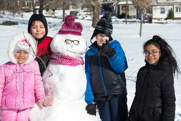 03/04/19 Wesley Bunnell | Staff Gatianna Valentin, age 5, Michael Yeung, age 9, Xavier Matias, age 9, and Lilianna Valentin, age 9 pose with the snowman they helped make at Walnut Hill Park on Monday afternoon while sledding with family and friends.