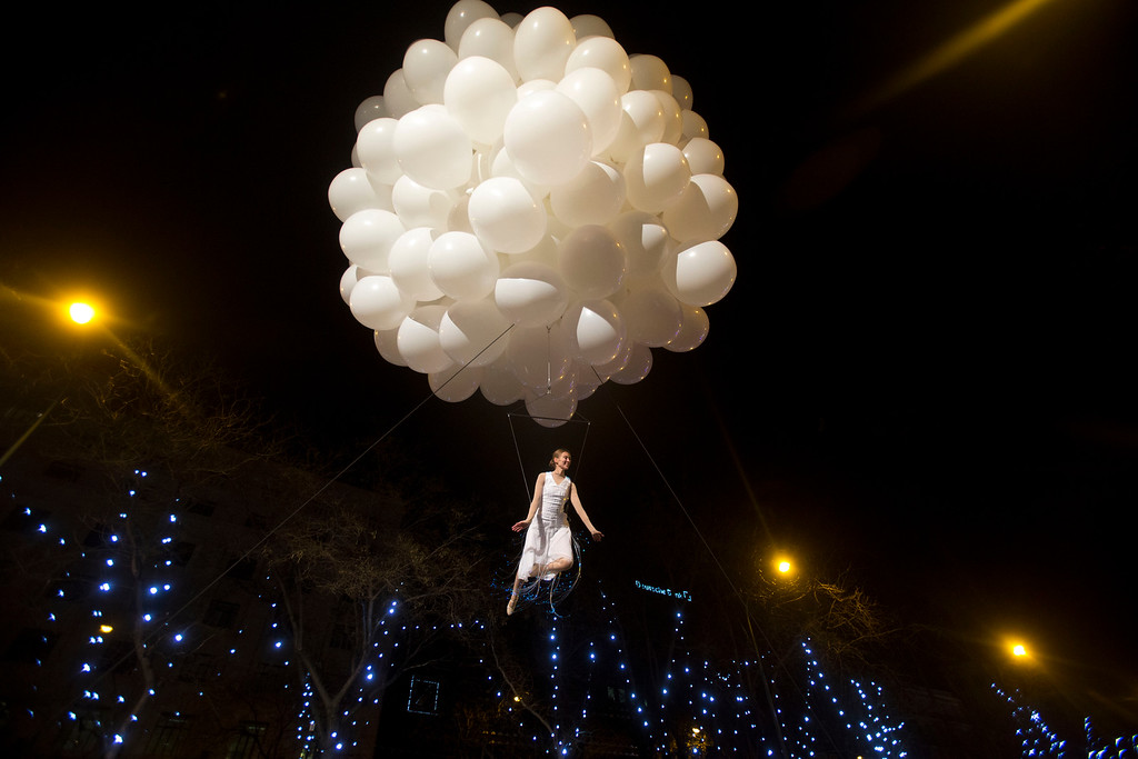 . An acrobatic performer floats in the air during the \'Cabalgata de Reyes\' or Epiphany parade in Madrid, Tuesday, Jan. 5, 2016. The traditional parade marks the eve of the Epiphany, a Christian holiday celebrating the story of the three wise men believed to have followed a bright star to offer gifts of gold, frankincense and myrrh to the newborn Jesus in Bethlehem. (AP Photo/Paul White)