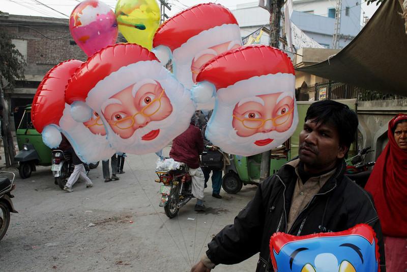 . Pakistani vendor Maqbool Mashi sells Santa Claus balloons ahead of Christmas in Lahore, Pakistan, Wednesday, Dec. 24, 2014. (AP Photo/K.M. Chaudary)