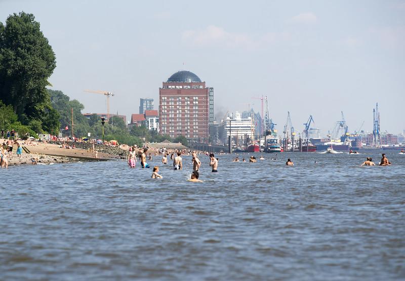 Elbstrand im Sommer mit Menschen die in der Elbe baden Museumshafen Oevelgönne Kreuzfahrtschiff Blohm und Voss und Elbphilharmonie