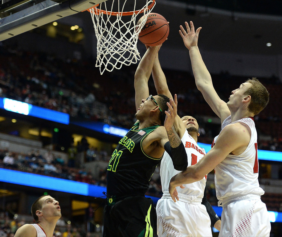 . Isaiah Austin #21 of the Baylor Bears goes up for a shot against Traevon Jackson #12 and Sam Dekker #15 of the Wisconsin Badgers in the first half during the regional semifinal of the 2014 NCAA Men\'s Basketball Tournament at the Honda Center on March 27, 2014 in Anaheim, California.  (Photo by Harry How/Getty Images)