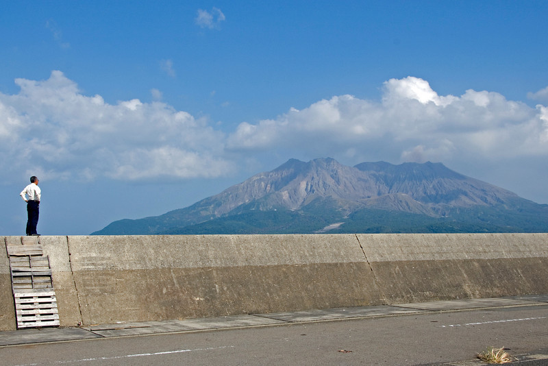 Man standing on wall with Mount Sakurajima in background