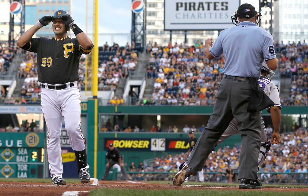 . Pittsburgh Pirates\' Tony Sanchez grabs his helmet after home plate umpire Chris  Guccione, right, called him out on strikes to end the first inning of the baseball game against the Colorado Rockies on Saturday, Aug. 3, 2013, in Pittsburgh. (AP Photo/Keith Srakocic)