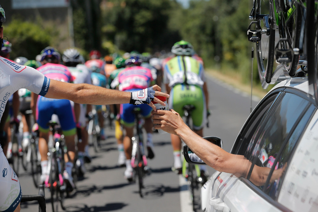 . Simon Geschke of Germany, left, collects water bottles from his team car during the seventh stage of the Tour de France cycling race over 205.5 kilometers (128.5 miles) with start in Montpellier and finish in Albi, southern France, Friday July 5, 2013. (AP Photo/Christophe Ena)