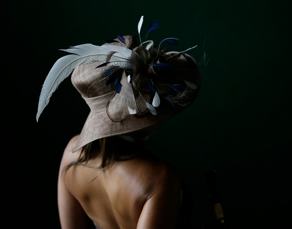 . A spectator arrives with her fancy hat to attend the 139th Kentucky Derby at Churchill Downs Saturday, May 4, 2013, in Louisville, Ky. (AP Photo/Matt Slocum)