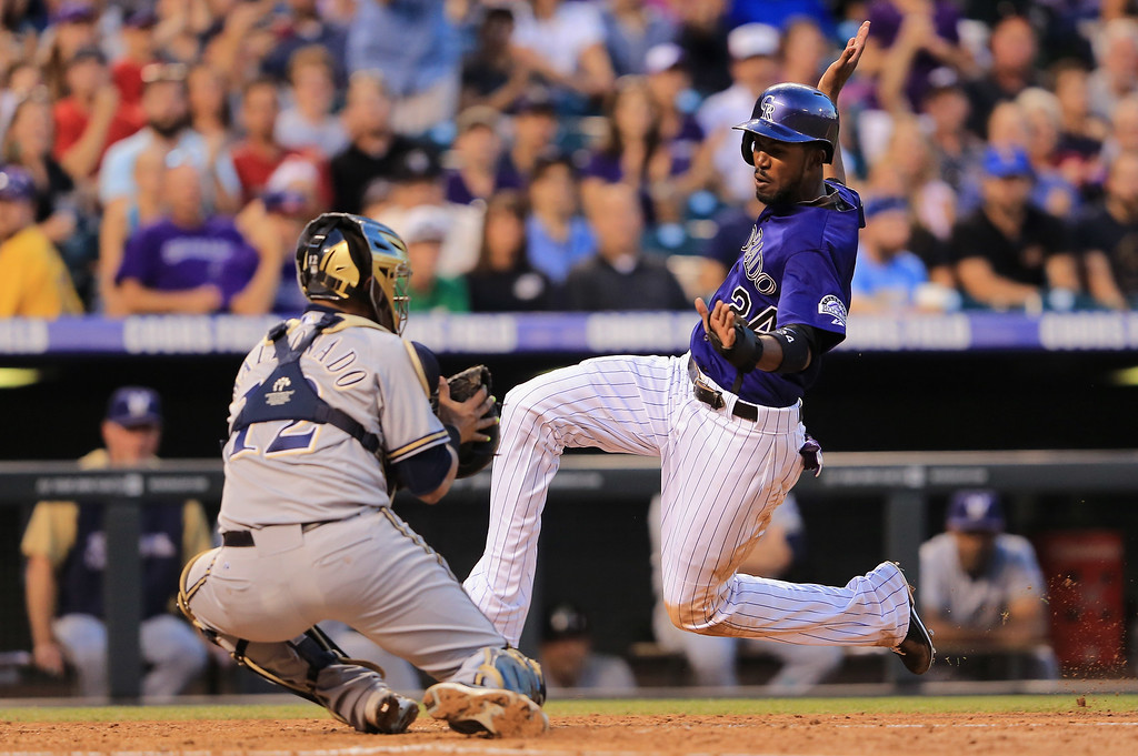 . DENVER, CO - JULY 26:  Dexter Fowler #24 of the Colorado Rockies is tagged out by catcher Martin Maldonado #12 of the Milwaukee Brewers as Fowler tried to score on a base hit by Troy Tulowitzki #2 of the Colorado Rockies in the fourth inning at Coors Field on July 26, 2013 in Denver, Colorado.  (Photo by Doug Pensinger/Getty Images)
