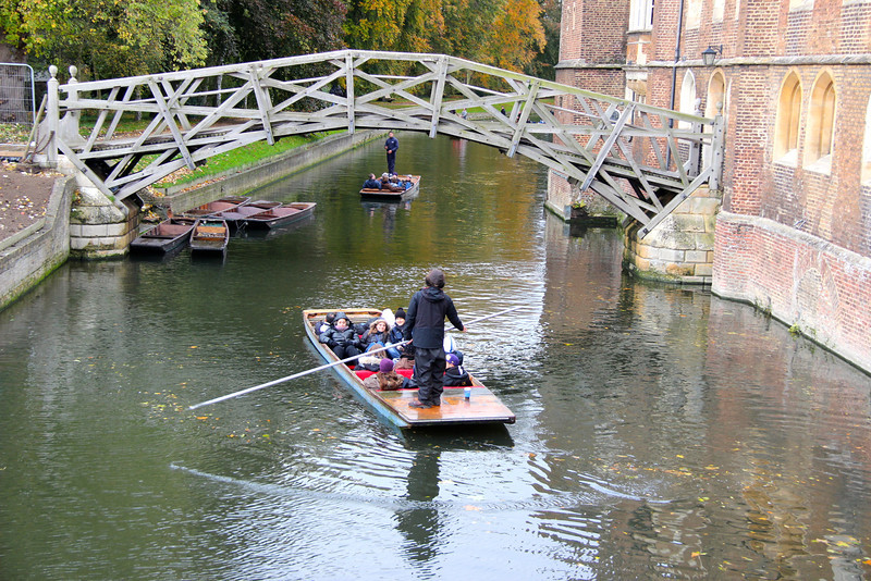 A student stands in a boat on the river cam near a bridge