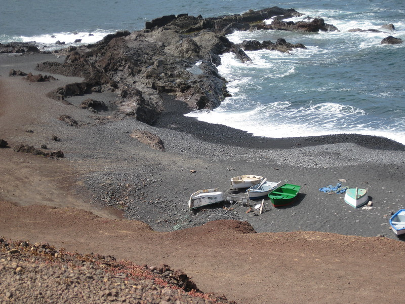 Black rock juts into the sea on a black sand beach in Lanzarote. A few colorful small boats are pulled up onto the sand.