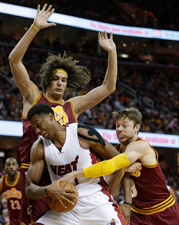 . Miami Heat�s Hassan Whiteside, middle, tries to get past Cleveland Cavaliers\' Anderson Varejao, back, from Brazil, and Cleveland Cavaliers\' Matthew Dellavedova, right, from Australia, during the second half of an NBA basketball game Friday, Oct. 30, 2015, in Cleveland. The Cavaliers won 102-92. (AP Photo/Tony Dejak)