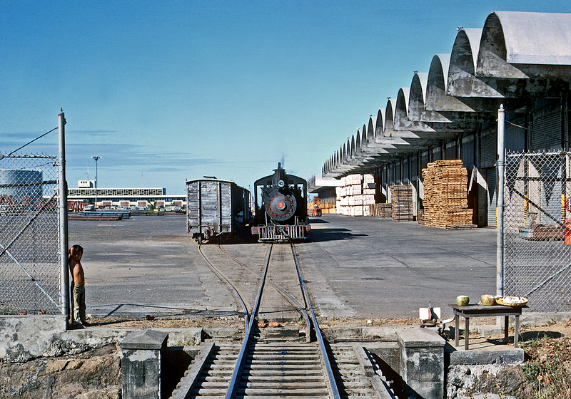January 1968.  FES 8, a 1896 product of Baldwin and still retaining its link and pin front coupling, contrasts with the modern port of Acajutla, which was the major reason for the FES' existence.  The new port replaced a much more modest facility a mile north.  Freight included inbound manufactured goods and petroleum products, and outbound coffee and sugar.  Meanwhile, a young entrepreneur waits for customers at his snack stand.