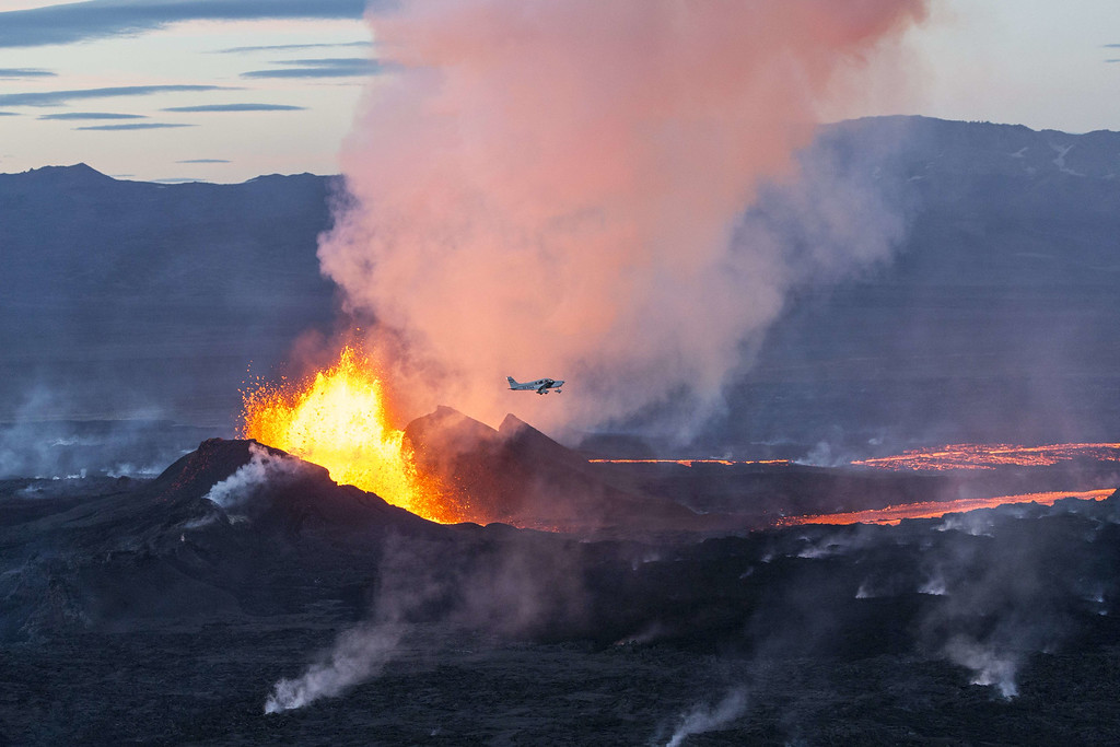 . An aerial picture taken on September 14, 2014 shows a plane flying over the Bardarbunga volcano spewing lava and smoke in southeast Iceland. The Bardarbunga volcano system has been rocked by hundreds of tremors daily since mid-August, prompting fears the volcano could explode. Bardarbunga, at 2,000 metres (6,500 feet), is Iceland\'s second-highest peak and is located under Europe\'s largest glacier, Vatnajoekull. BERNARD MERIC/AFP/Getty Images