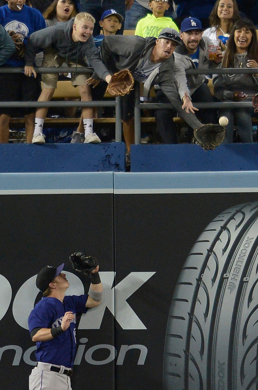 . A fan reaches out for a Matt Kemp home run ball while Rockies Corey Dickerson can only watch it sail over the left field wall in the bottom of the 4th inning. The Dodgers played the Colorado Rockies at Dodger Stadium in Los Angeles, CA. 6/18/2014(Photo by John McCoy Daily News)