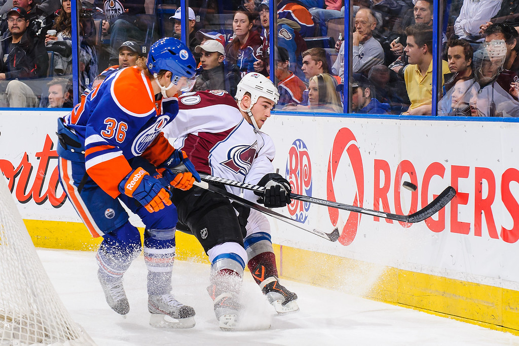 . EDMONTON, AB - DECEMBER 5: Philip Larsen #36 of the Edmonton Oilers battles for the puck against Ryan O\'Reilly #90 of the Colorado Avalanche during an NHL game at Rexall Place on December 5, 2013 in Edmonton, Alberta, Canada. The Oilers defeated the Avalanche 8-2. (Photo by Derek Leung/Getty Images)
