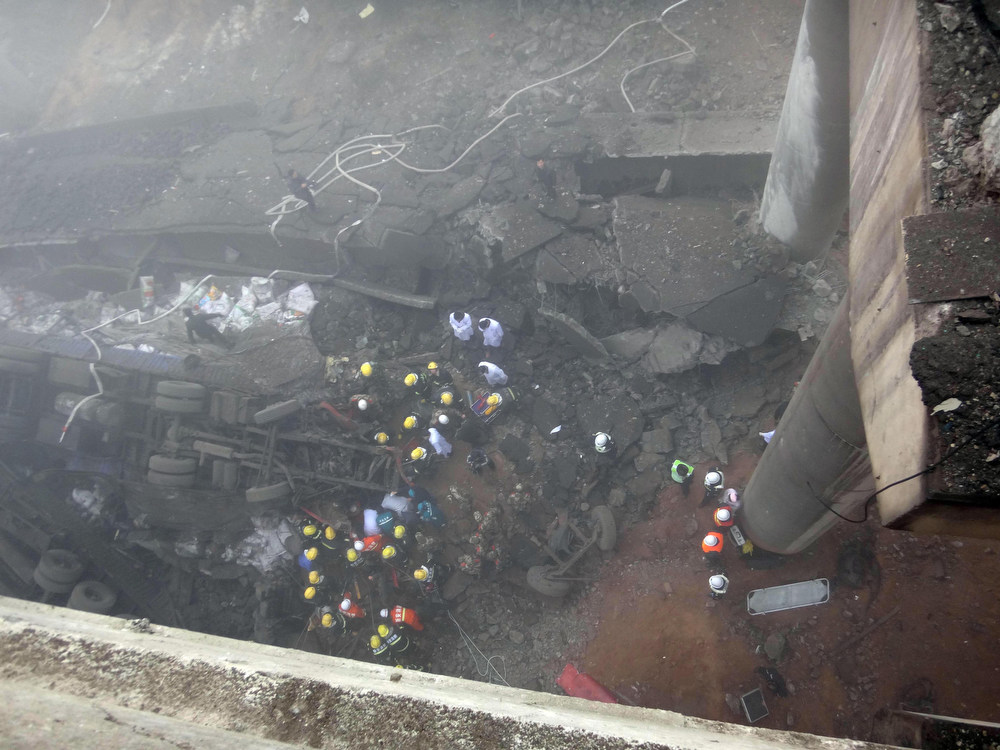 Description of . In this photo provided by China's Xinhua News Agency, rescuers work at the accident site where an expressway bridge partially collapsed due to a truck explosion in Mianchi County, Sanmenxia, central China's Henan Province, Thursday, Feb. 1, 2013.  Fireworks for Lunar New Year celebrations exploded on a truck in central China, destroying part of an elevated highway Friday and sending vehicles plummeting 30 meters (about 100 feet) to the ground. State media had conflicting reports on casualties.  (AP Photo/Xinhua, Xiao Meng)
