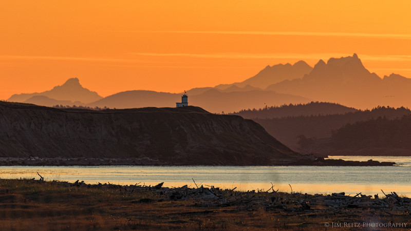 Telephoto shot of the Cattle Point Light on San Juan Island, silhouetted just before sunrise against the distant Cascade Mountains on the mainland.