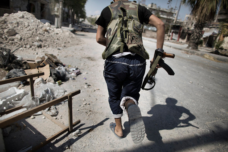 . A Syrian rebel fighter runs in a sniper alley in the Saif al-Dawla neighbourhood of Aleppo on September 12, 2012. Syrian rebels have vowed to retake control of the large Hanano army base in Aleppo, a few days after loosing control of it to Syrian government forces . MARCO LONGARI/AFP/Getty Images