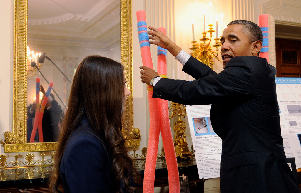 . President Barack Obama talks with Elana Simon, 18, of New York City, about her cancer research project that is part of the 2014 White House Science Fair exhibit on display in the State Dining Room of the White House in Washington, Tuesday, May 27, 2014. Simon, at age 12, was diagnosed with fibrolamellar hepatocellular carcinoma, a little-known form of cancer that affects the liver. After surviving the disease, she now helps scientists research the genetics behind it. Obama was celebrating the student winners of a broad range of science, technology, engineering and math (STEM) competitions from across the country. (AP Photo/Susan Walsh)