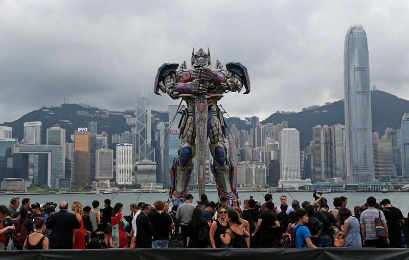 """. People gather in front of a giant figure of Optimus Prime from the movie \""""Transformers 4: Age of Extinction,\"""" displayed for its world premiere in Hong Kong Thursday, June 19, 2014. The latest installment in the blockbuster series of \""""Transformers\"""" films is making its world premier not in the usual entertainment hubs of Los Angeles or New York but in the wealthy Chinese metropolis of Hong Kong, the latest sign of Hollywood\'s increasing focus on China\'s booming film market. (AP Photo/Kin Cheung)"""