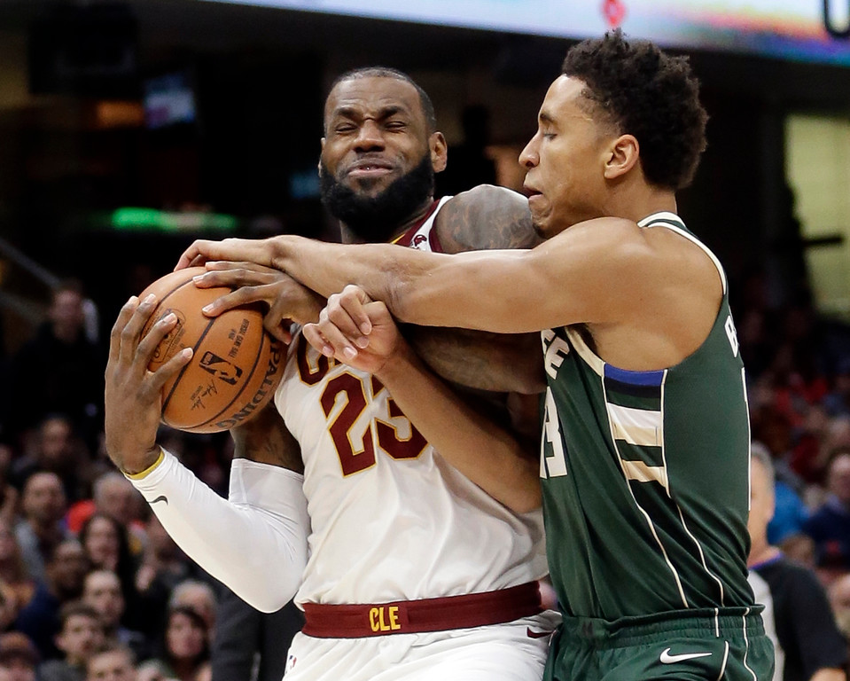 . Cleveland Cavaliers\' LeBron James, left, is fouled by Milwaukee Bucks\' Malcolm Brogdon in the first half of an NBA basketball game, Tuesday, Nov. 7, 2017, in Cleveland. (AP Photo/Tony Dejak)