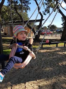 Every Sunday is an adventure when you are two. A girl in a sun hat on swing and looking in the distance to her left