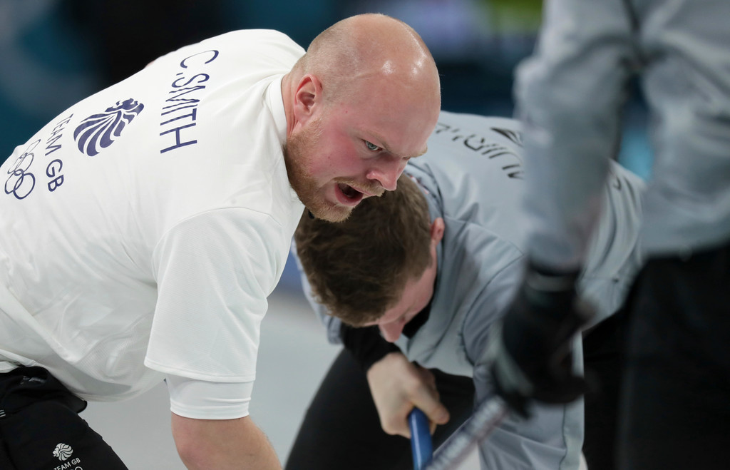 . Britain\'s Cameron Smith reacts as he sweeps ice with his teammate during their men\'s curling match against Italy at the 2018 Winter Olympics in Gangneung, South Korea, Sunday, Feb. 18, 2018. (AP Photo/Aaron Favila)