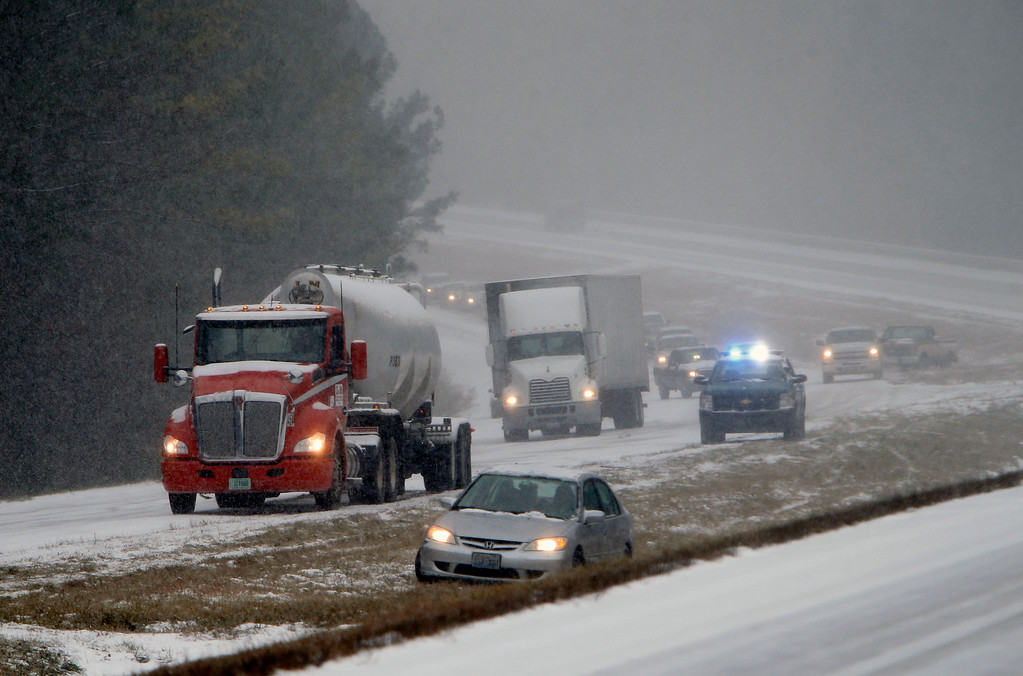 . Vehicles are backed up on a snow covered US Highway 280 during a snow storm, Tuesday, Jan. 28,  2014 in Chelsea, Ala. A fast-moving, unexpectedly severe winter storm blanketed much of Alabama with a treacherous layer of frozen precipitation Tuesday, causing multiple wrecks, stranding hundreds of children in schools and coating palm trees with ice at the beach.  (AP Photo/Hal Yeager)