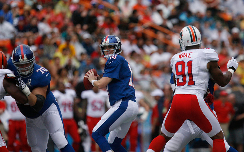 . New York Giants quarterback Eli Manning (C) of the NFC prepares to pass the ball as Miami Dolphins defensive end Cameron Wake (91) of the AFC watches during the second quarter the NFL Pro Bowl at Aloha Stadium in Honolulu, Hawaii January 27, 2013. REUTERS/Hugh Gentry