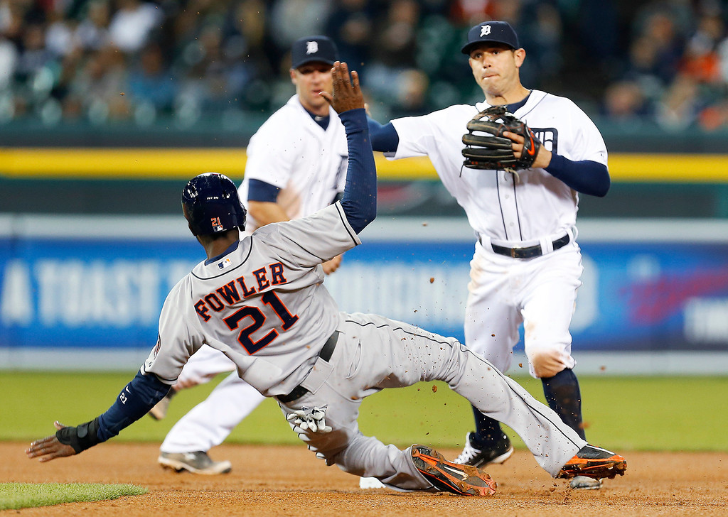 . Houston Astros\' Dexter Fowler (21) tries to distract Detroit Tigers second baseman Ian Kinsler as he throws to complete a double play on a Jason Castro ground ball in the sixth inning of a baseball game in Detroit, Wednesday, May 7, 2014. (AP Photo/Paul Sancya)