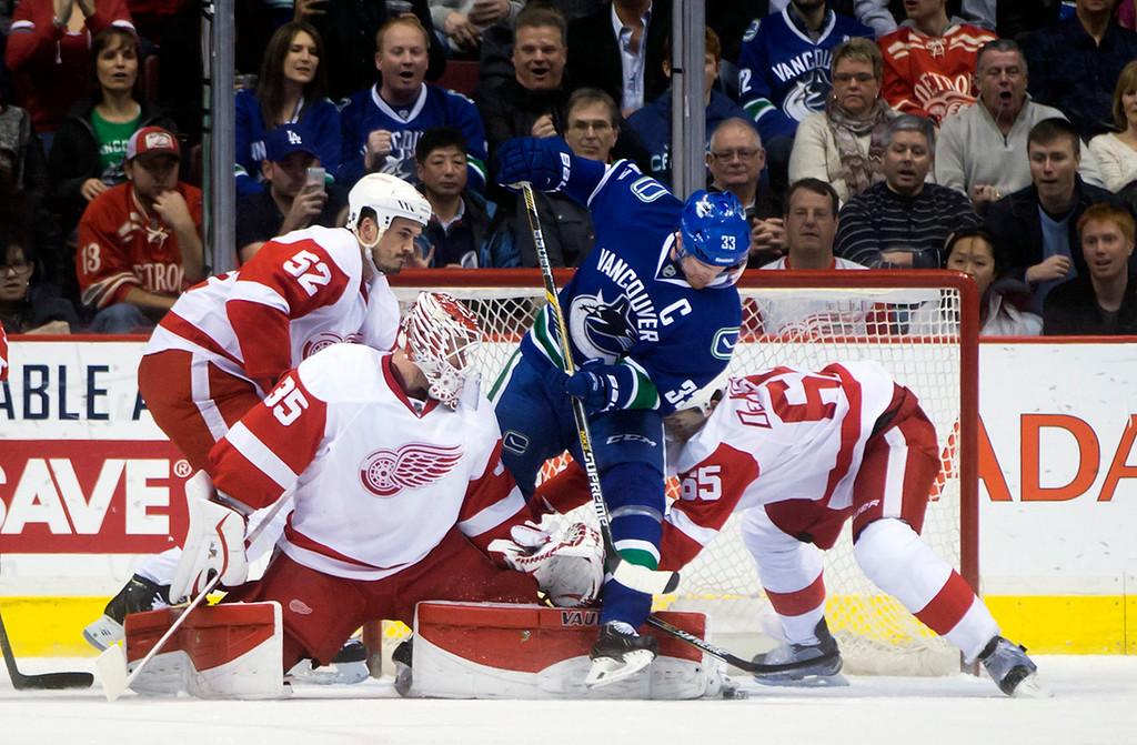 . Vancouver Canucks\' Henrik Sedin, second from right, of Sweden, digs for the puck under Detroit Red Wings goalie Jimmy Howard (35) as Jonathan Ericsson, of Sweden, (52) and Danny DeKeyser (65) defend during the first period of an NHL hockey game in Vancouver, British Columbia on Saturday, Jan. 3, 2015. (AP Photo/The Canadian Press, Darryl Dyck)