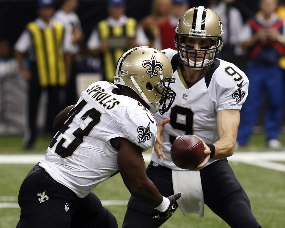 . New Orleans Saints quarterback Drew Brees (9) hands off to running back Darren Sproles on a touchdown carry in the first half of an NFL football game in New Orleans, Monday, Sept. 30, 2013. (AP Photo/Bill Haber)