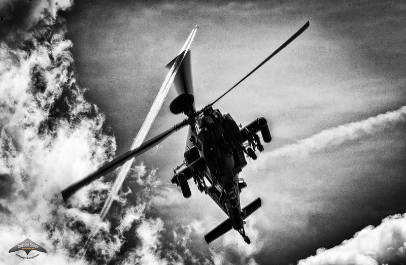 Boeing AH-64 Apache Longbow at RIAT 2015 with airliner contrails above.