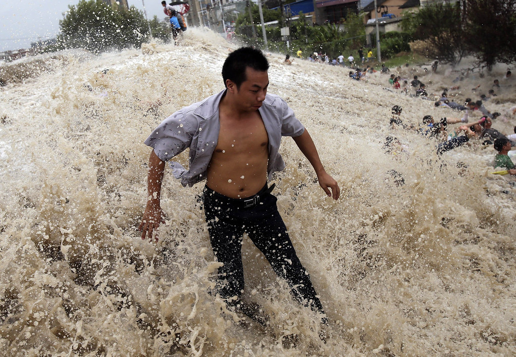 """. This picture taken on August 22, 2013 shows onlookers (R) being washed away from huge waves from the \""""Haining tide\"""" - a daily occurrence when the river tides hit the banks of the city - as the waves surged higher than usual due to the influence of Typhoon Trami in the region in Haining, in eastern China\'s Zhejiang province. State media reported on August 23 that 30 people were injured and 11 still in hospital after the wave hit.  Typhoon Trami, the 12th typhoon to hit China this year, brought rainstorms and wreaked havoc in eastern China after landing in Fujian Province early on August 22.         AFP PHOTOSTR/AFP/Getty Images"""