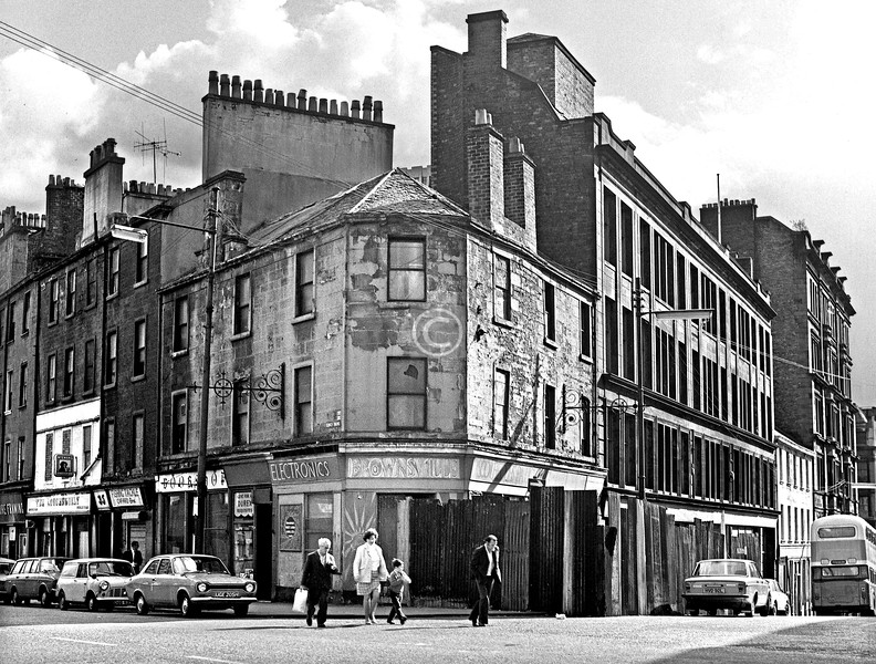 Corner of Cowcaddens St and  Renfield St.  Shops in Cowcaddens St, from the left: Picture Framing / the Loughswilly Bar / Fishing Tackle, Cafaro Bros. / Bookshop / Agent for all Durex requisites / Brownsville Electronics.     October 1975