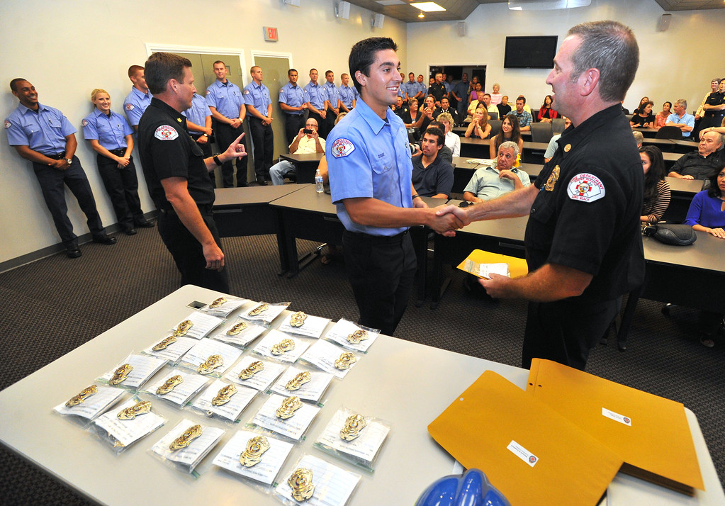 . LONG BEACH - 08/02/2013  (Photo: Scott Varley, Los Angeles News Group)  25 new ambulance drivers graduated from the Long Beach Fire Department\'s two week training academy and received their LBFD badges during a short ceremony. Jeff Cusick, center, receives his badge during the ceremony.