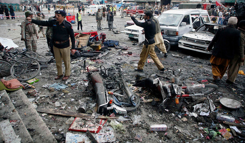 . Police officials investigate at the scene of a bomb explosion in Quetta January 10, 2013. A bomb blast in a crowded marketplace killed 11 people and injured more than 40 in Pakistan\'s eastern provincial capital of Quetta on Thursday and a local militant group claimed responsibility, police said. REUTERS/Naseer Ahmed